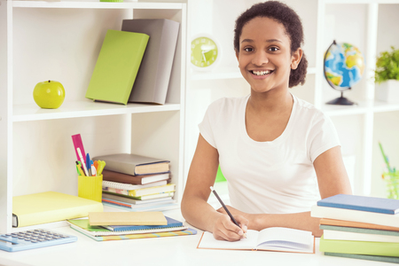 Young pretty smiling mulatto schoolgirl sitting at the table and holding a pencil in hand on colorful background. Standard-Bild