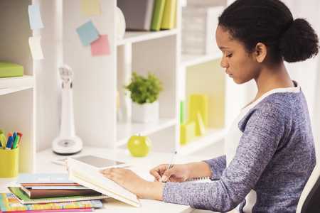 Young pretty  mulatto schoolgirl sitting at the table and writing homework on colorful background. Standard-Bild