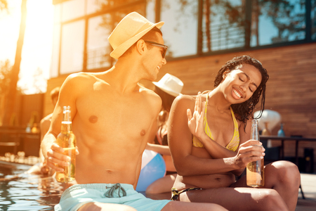 Young guy in summer straw hat flirts with girl in swimsuit that avoids him at swimmingpool. Joyful company spends leisure time in pool.