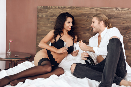 Longhaired man in shirt opens bottle of champagne in bed with sexy woman in black lingerie. Romantic encounter. Intimate relationship. Sexual relations.