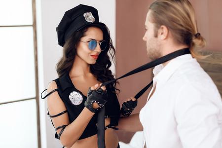 Passionnée jeune femme en uniforme de police décolle avec une cravate d'un homme aux cheveux longs dans la chambre. Jeux de rôles sexuels. Relation intime. Relations sexuelles. Banque d'images