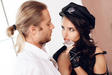 Woman in police uniform opens condom with mouth, looking at long haired man. Safe sex. Intimate relationship. Intimacy. Stock Photo