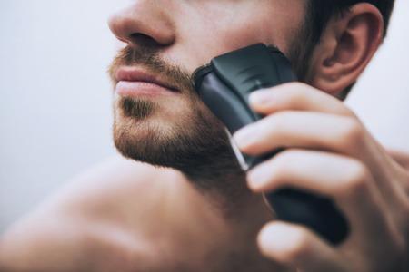 Man is shaving his face with electric razor looking in mirror in bathroom in morning. Banco de Imagens