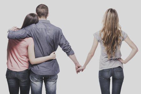 Love triangle. Handsome man embrace his girlfriend while holding hands with another girl. isolated on white background.