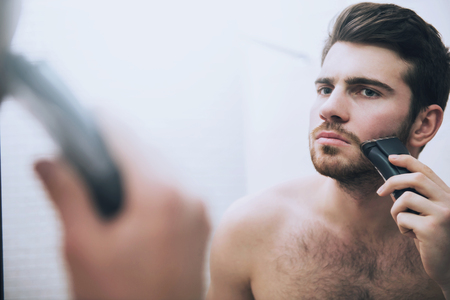 Man is shaving his face with electric razor looking in mirror in bathroom in morning. Stockfoto