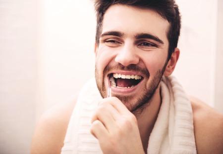남자는 아침에 화장실에서 어깨에 수건으로 그의 이빨을 닦고있다.