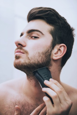 Man is shaving his face with electric razor looking in mirror in bathroom in morning. 写真素材