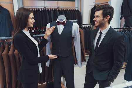 Beautiful elegant girl demonstrates three piece suit on mannequin in men costume store. Boutique of business suits. Consumerism Concept. Stock Photo