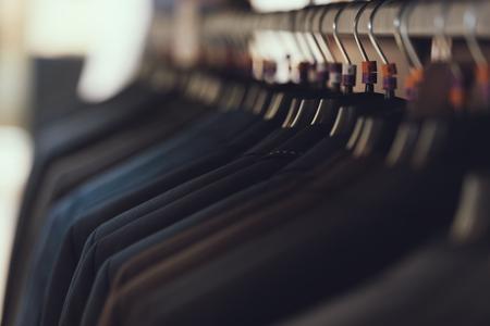 Ścieśniać. Męskie garnitury biznesowe wiszą na wieszakach w butiku z odzieżą biznesową. Duży wybór garniturów. Szafa. Przebieralnia.