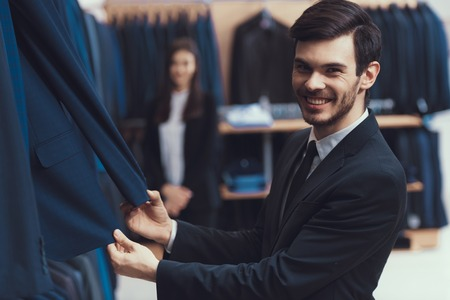 Smiling successful young man checks quality of jacket fabric in mens clothing store. Boutique of business suits. Foto de archivo - 100841326