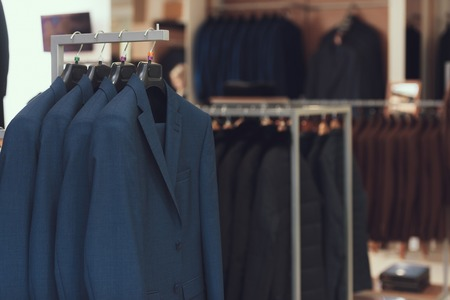 Business mens suits hang on hangers in boutique of business clothes. Big choice of suit. Wardrobe. Dressing room.