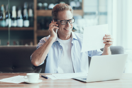 Confident businessman talking on phone, sitting at table in cafe. Smart businessman is discussing deal. Imagens - 100726399