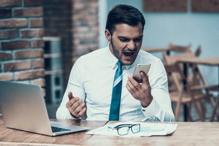 Uomo d'affari indiano arrabbiato che grida al telefono in ufficio. Esaurimento nervoso.