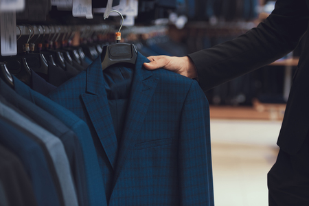 Businessman chooses business jacket among clothes hanging on hangers in clothing store. Boutique of business suits.