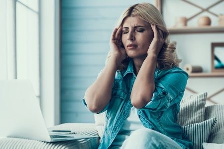 Blonde woman has headache in working with laptop. Fatigue from work.