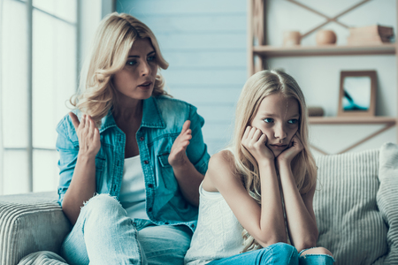 Blonde adult mother brings up naughty girl teenager. Concept of correct parenting. Banco de Imagens