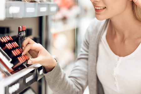 Blonde buys lipstick in cosmetics store. Shopping concept. Zdjęcie Seryjne - 100928521