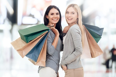 Young girlfriends with shopping bags are shopping at mall. Shopping concept. Consumerism concept. Sale.