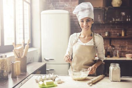 Mooie jonge vrouw in chef-kok hoed is beslag mengen, camera kijken en glimlachen tijdens het bakken in de keuken thuis