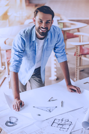 Attractive designer in casual clothes is looking at camera and smiling while working on drafts in studio