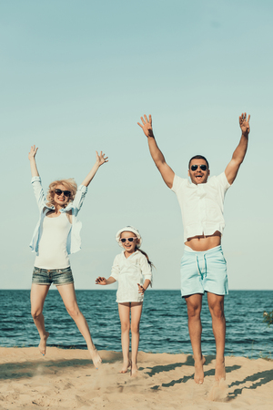 Young family sports on beach, jumping on sand. Family holiday at seaside.