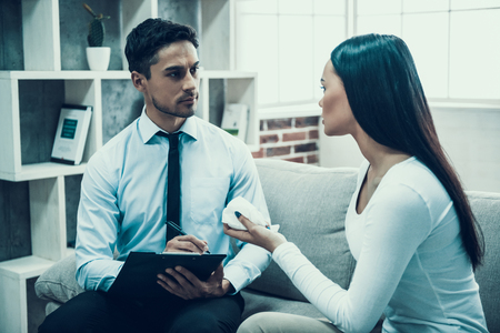 Experienced psychologist listens attentively to frustrated woman. Psychological help to oppressed. Stock Photo