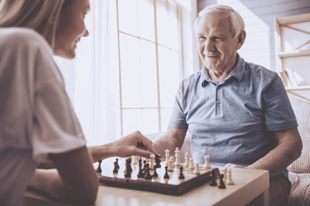 Beautiful young girl-volunteer and handsome old man are playing chess and smiling