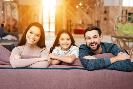A man, a woman and their little daughter are posing on the camera while sitting on the couch. They are in a store selling home furniture. They are in a very good mood. Stok Fotoğraf