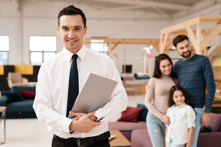 Furniture retailer in the store looking at the camera. Behind him stands a young family with a little girl. They came to buy new furniture. Stockfoto