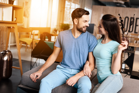 A guy and a girl in a furniture store. They came to choose new furniture for their apartment. They have a good mood. Banco de Imagens
