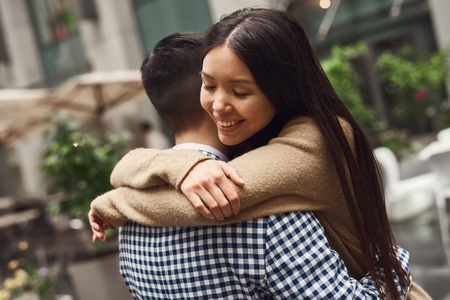 Girl with guy romantically hugging on building background. Love story.