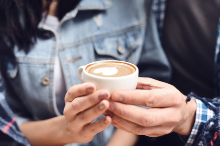 Close up. Guy with a girl holding a cup of coffee. Romantic concept. Archivio Fotografico