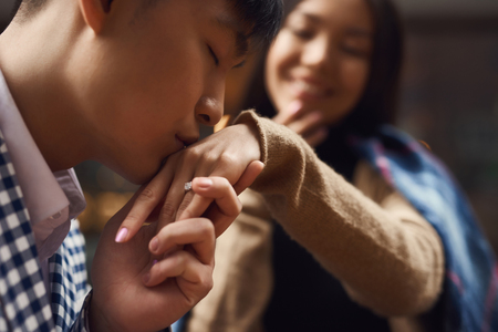 Guy kisses hand of girl sitting at table in cafe. Romantic concept Stockfoto