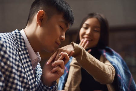 Guy kisses hand of girl sitting at table in cafe. Romantic concept Stock Photo - 101429733