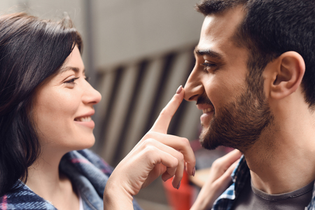 Happy girl touches a guy nose. Romantic concept.
