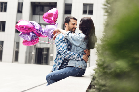 Loving couple hugging sitting on parapet with balloons. Stock Photo