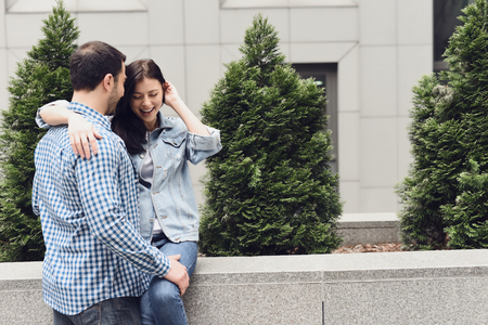 Loving couple hugging sitting on parapet. Love story. Anniversary concept. Stock Photo