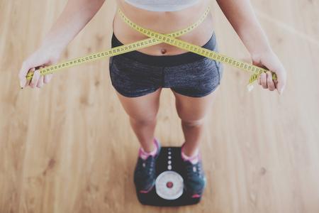 Bovenaanzicht van vrij slanke vrouw met maatregel rond haar lichaam staande op de weegschaal. Stockfoto