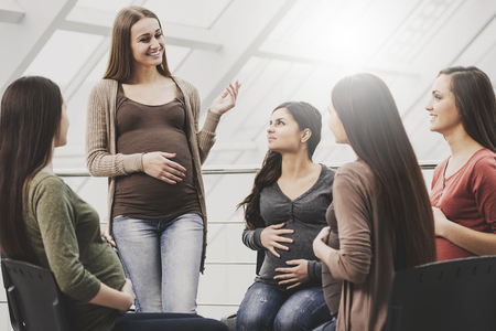 Happy pregnant girl holding her stomach speaks to friends .Preparation and expectation concept.