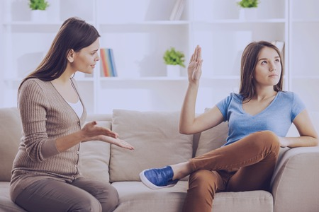 Teen girl showing stop gesture to angry mother while sitting on sofa at home.Problems in family concept. 写真素材
