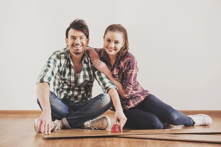 Portrait of bearded guy who measures laminate. His wife sitting next to him. Repair in new apartment.