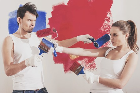 Merry couple having fun with paint rollers in new apartment. Young couple doing repairs in apartment.