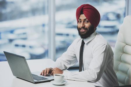 Joven empresario barbudo indio trabajando detrás de la computadora portátil en la oficina moderna. Gente de negocios.