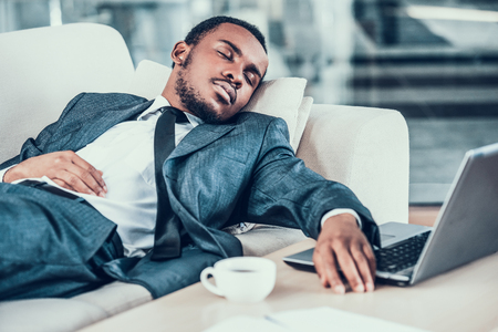 Tired african bearded businessman asleep on sofa in office.Business people.Rest in office.