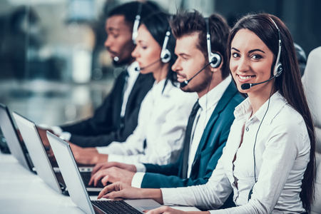 Empleados felices jóvenes multiculturales en call center sentados en computadoras y trabajando. Trabajo en equipo. Empleados en auriculares.