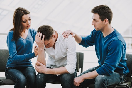 Feeling pain and depression. Depressed young man sitting at chair while two other people comforting his.