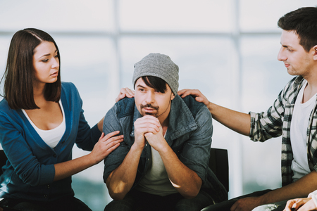 White bearded man in depression sits on chair while two troubled people on sides support him.Group therapy. Фото со стока