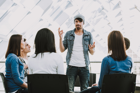 Young bearded man shares problems with other people. People in circle listen to man.Support group.