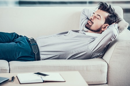 Tired bearded businessman asleep on sofa in office.Business people.Rest in office. Stock Photo