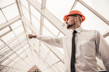 Young bearded architect in helmet in building points finger at something. Stock Photo